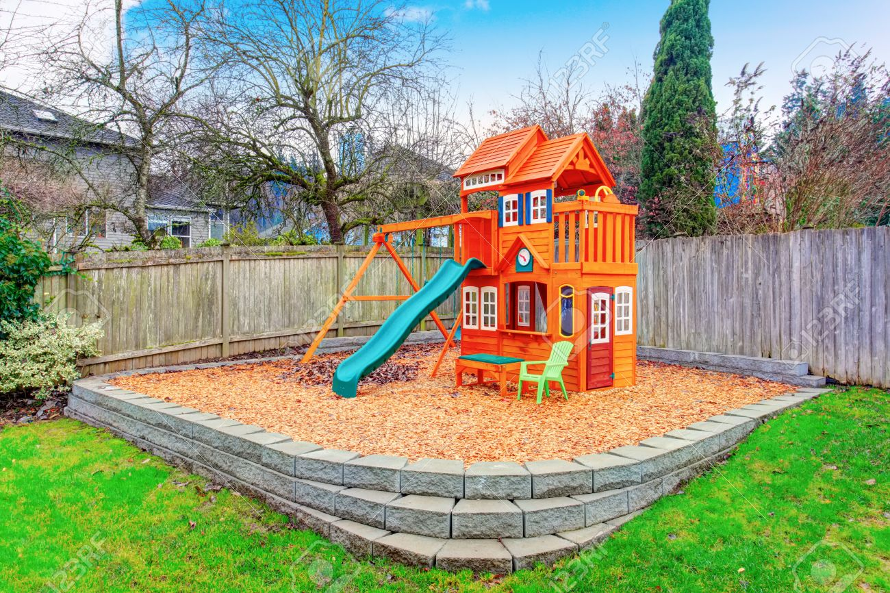 fenced backyard with wooden playground for kids stock photo