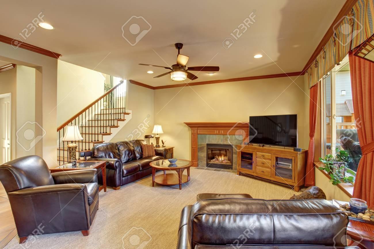 Luxe salon intérieur avec cheminée et de la moquette. canapé en cuir noir  et des fauteuils, rideaux oranges