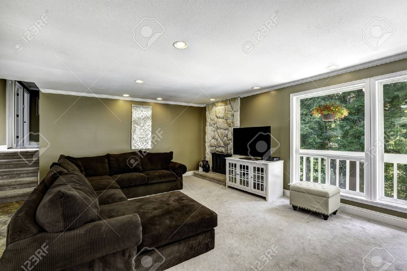 American Family Room Interior With Brown Velvet Sofa Set And Fireplace With  Stone Decor Stock Photo