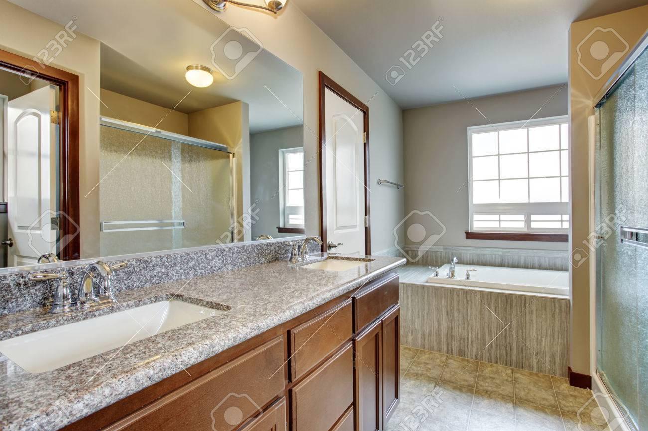 Interni bel bagno con mobiletto vanità e grande specchio doccia