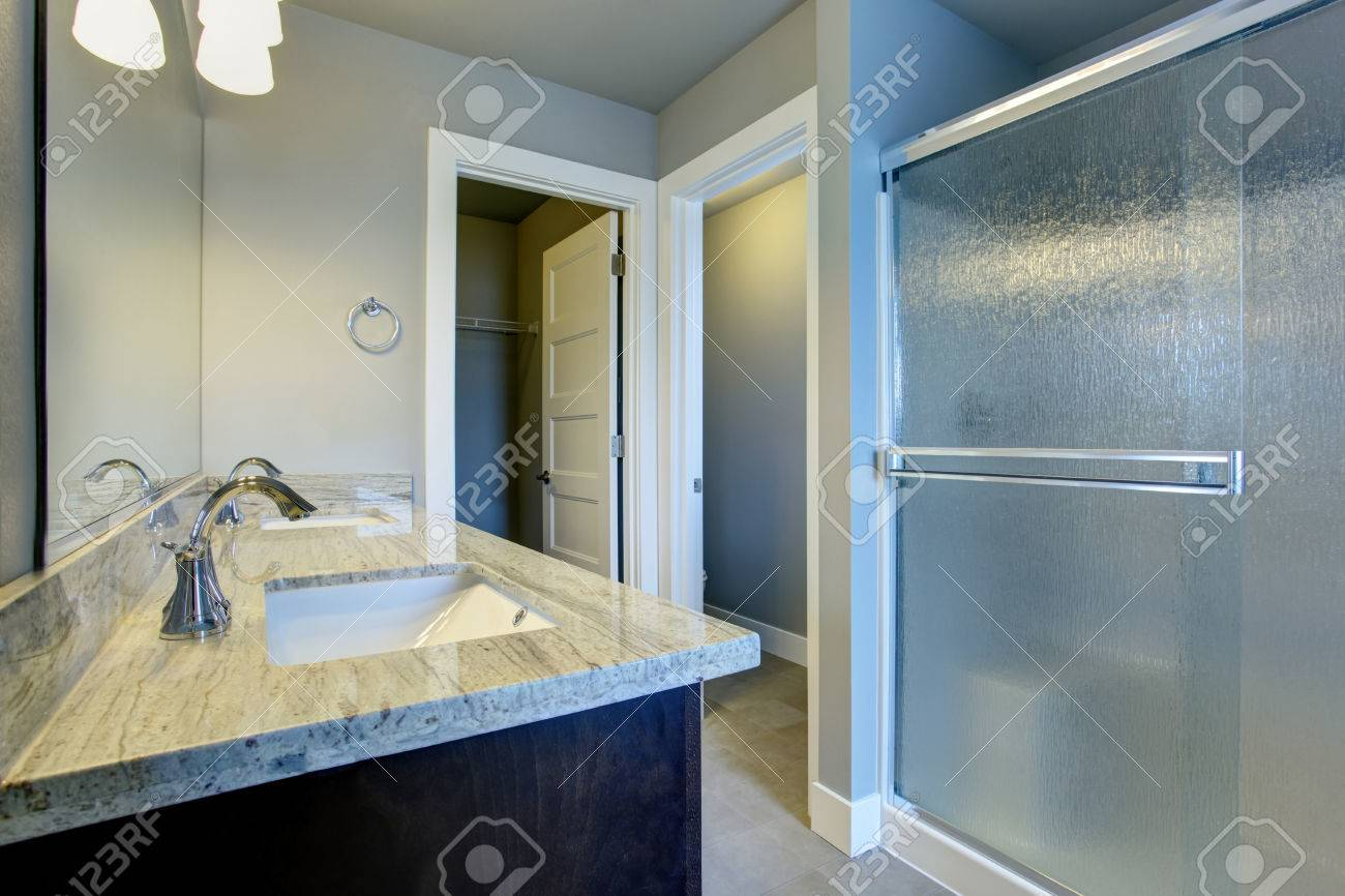 Bright bathroom interior with glass shower and tile floor and bright bathroom interior with glass shower and tile floor and walk in closet stock photo dailygadgetfo Choice Image
