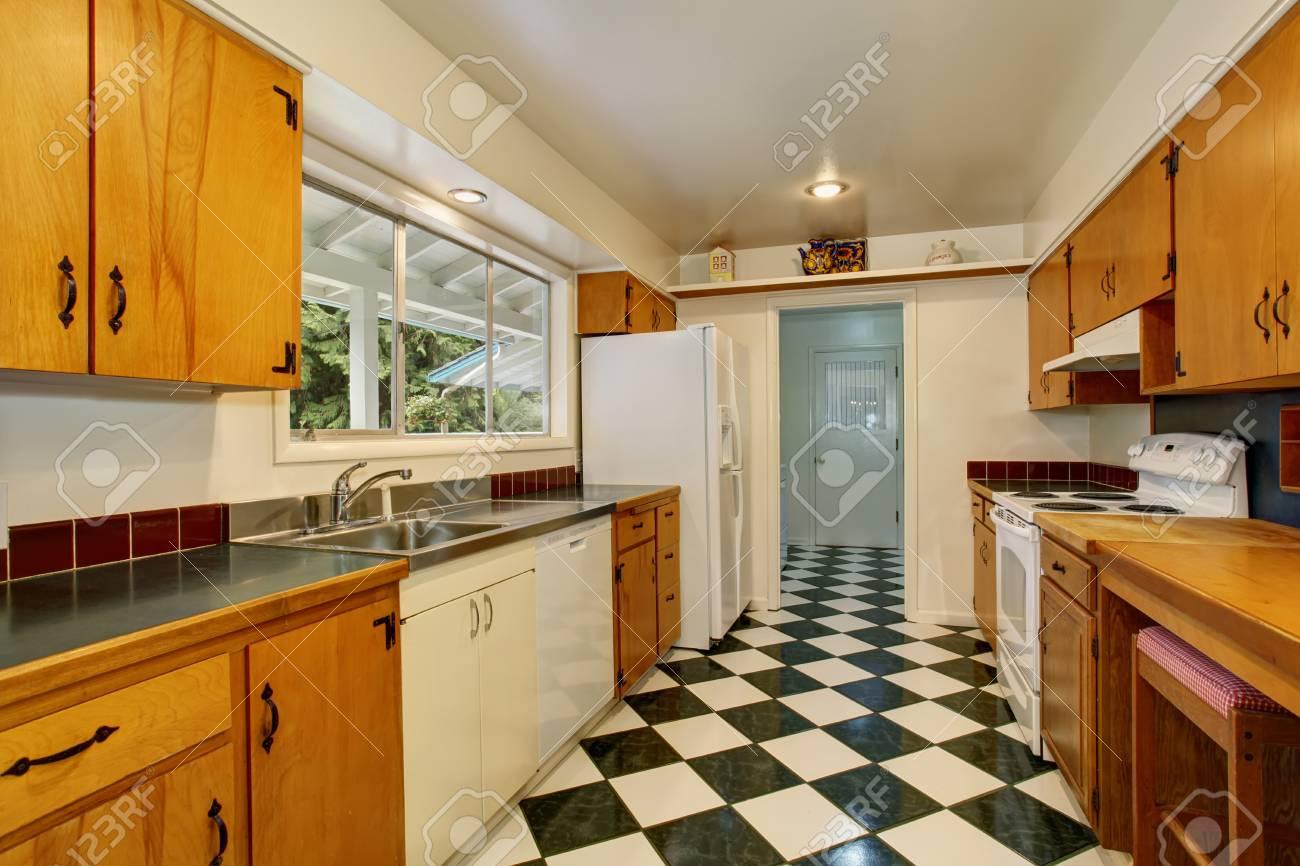 Intérieur étroit de la cuisine avec carrelage noir et blanc, armoires  marron clair et appareils de cuisine blancs.