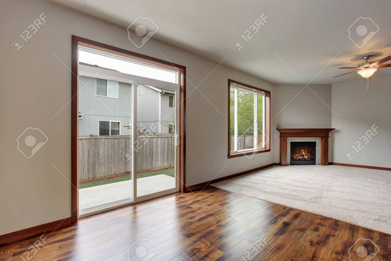 Large empty living room interior with carpet floor, fireplace..
