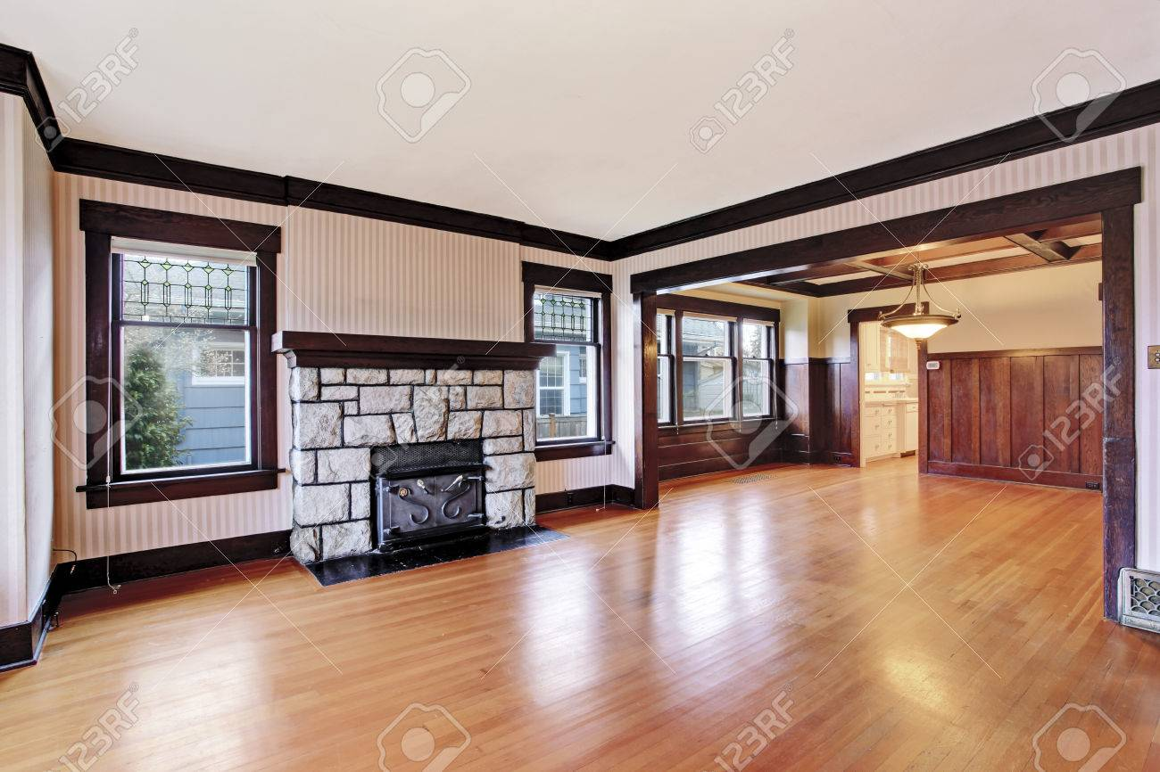 Empty Family Room With White Ceiling And Dark Brown Trim Antique Stone Fireplace Hardwood