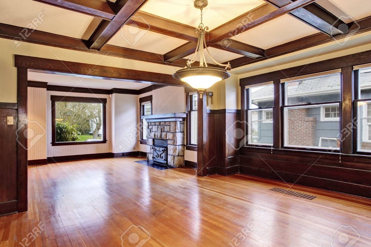 empty room with wood paneled walls and coffered ceiling view of family room with old - Wood Paneling With Wood Floor