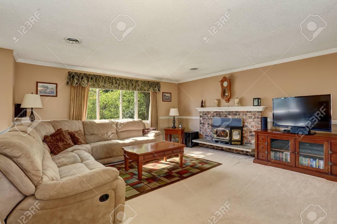 Tapis Et Canapé D Angle salon dans des tons crémeux avec canapé d'angle et cheminée en brique.  belle table basse en bois sur un tapis coloré.