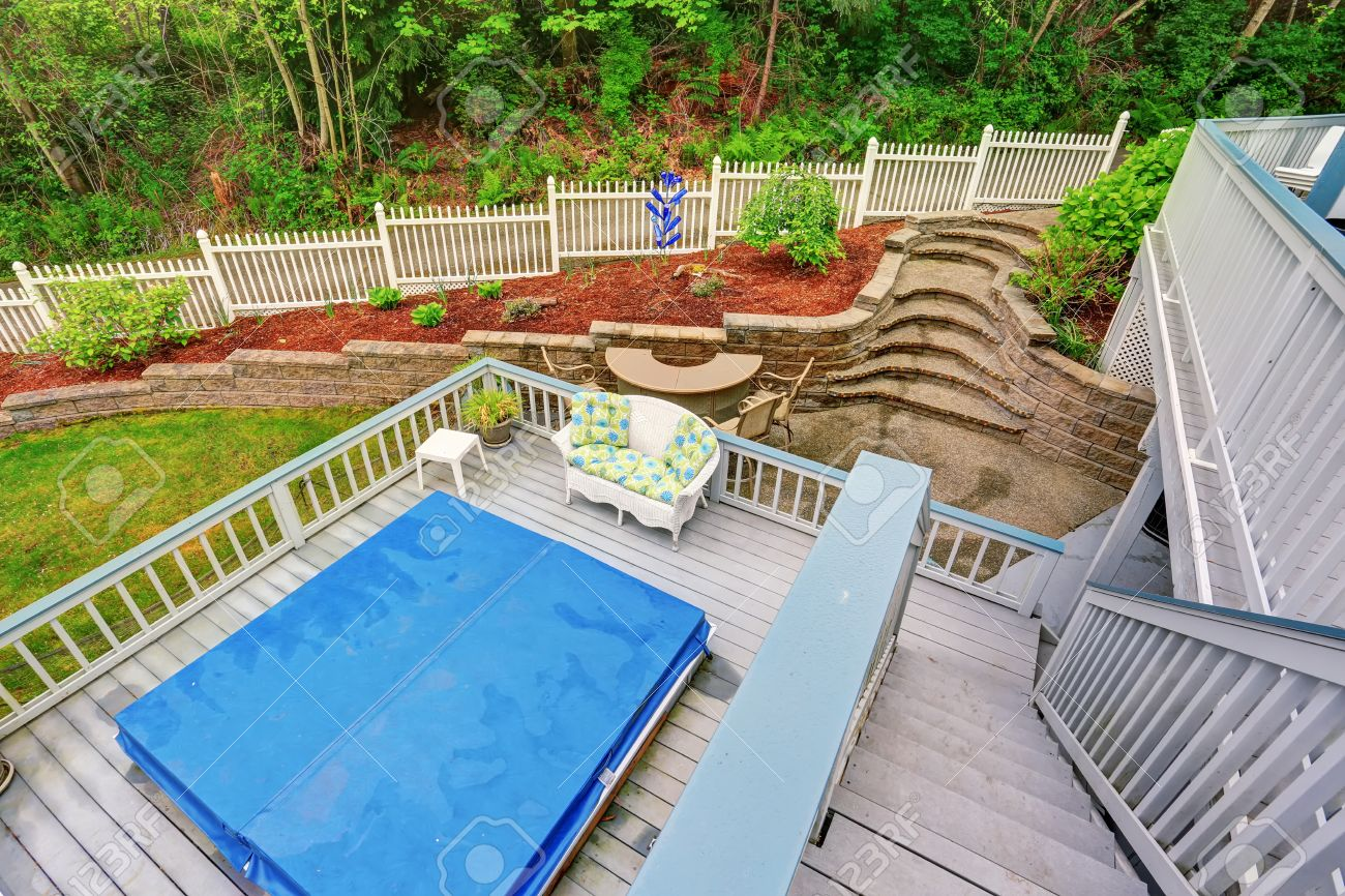 two level backyard deck with jacuzzi on the first floor and patio