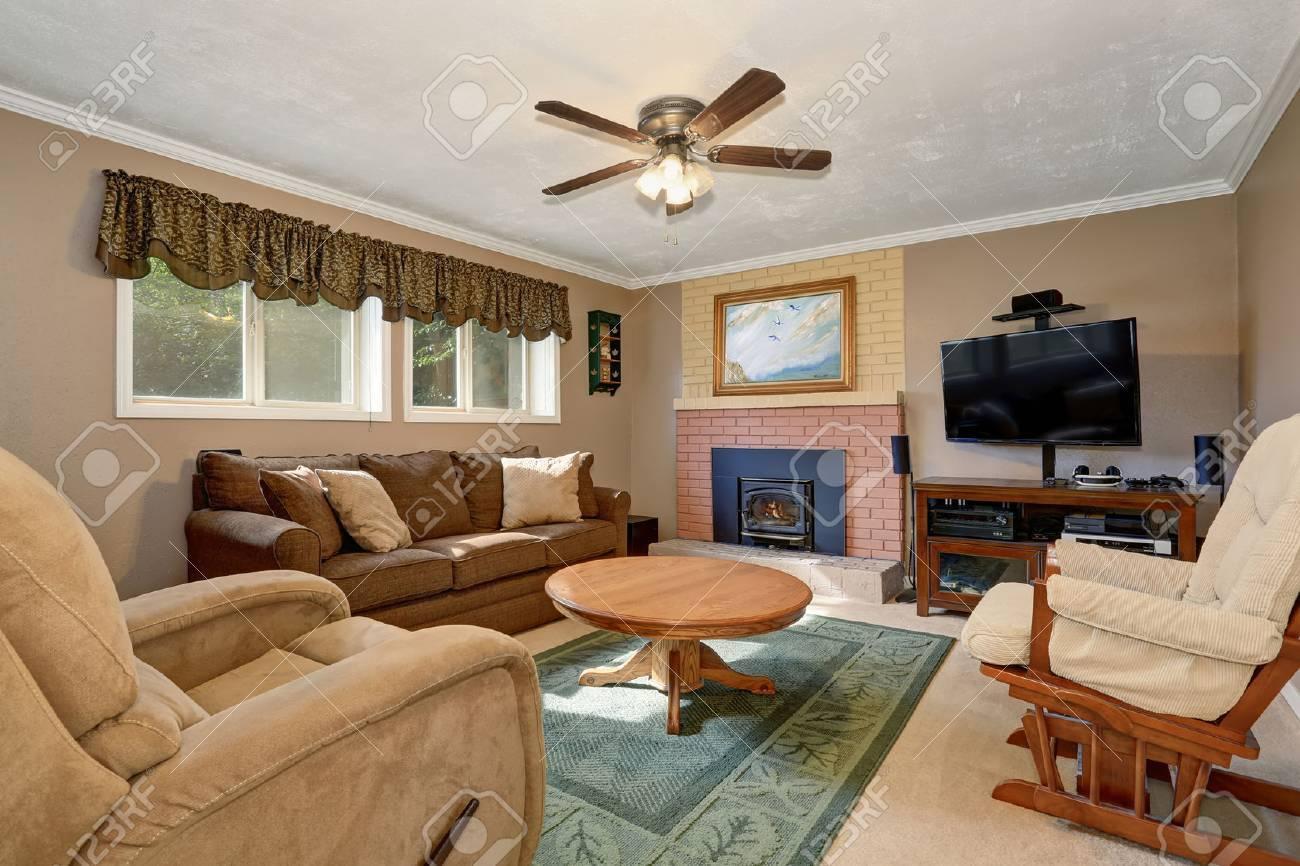 Typique salon américain avec canapé brun, chaise berçante, table basse  ronde en bois et cheminée de carreaux de briques.