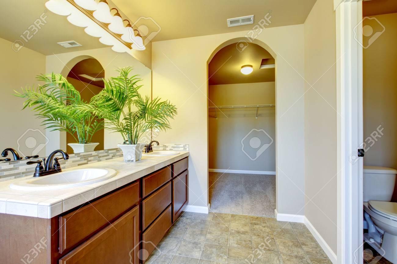 Intérieur de la salle de bains dans des tons beiges avec meuble-lavabo  marron moderne avec le dessus de tuile, deux éviers et un grand miroir. ...