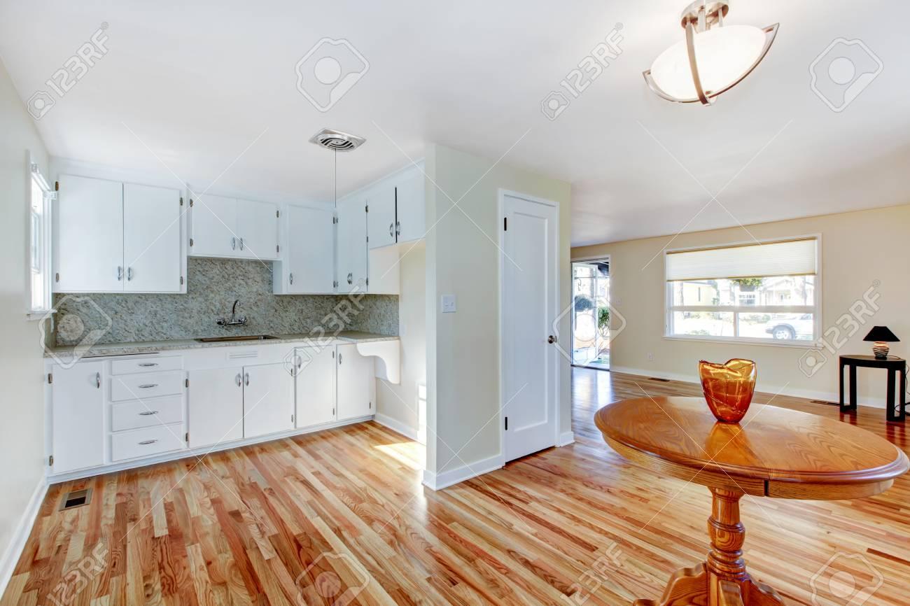 Muebles de cocina blancas con electrodomésticos de acero y piso de madera  tono ligero. Plan de piso abierto. Noroeste, EE.UU.