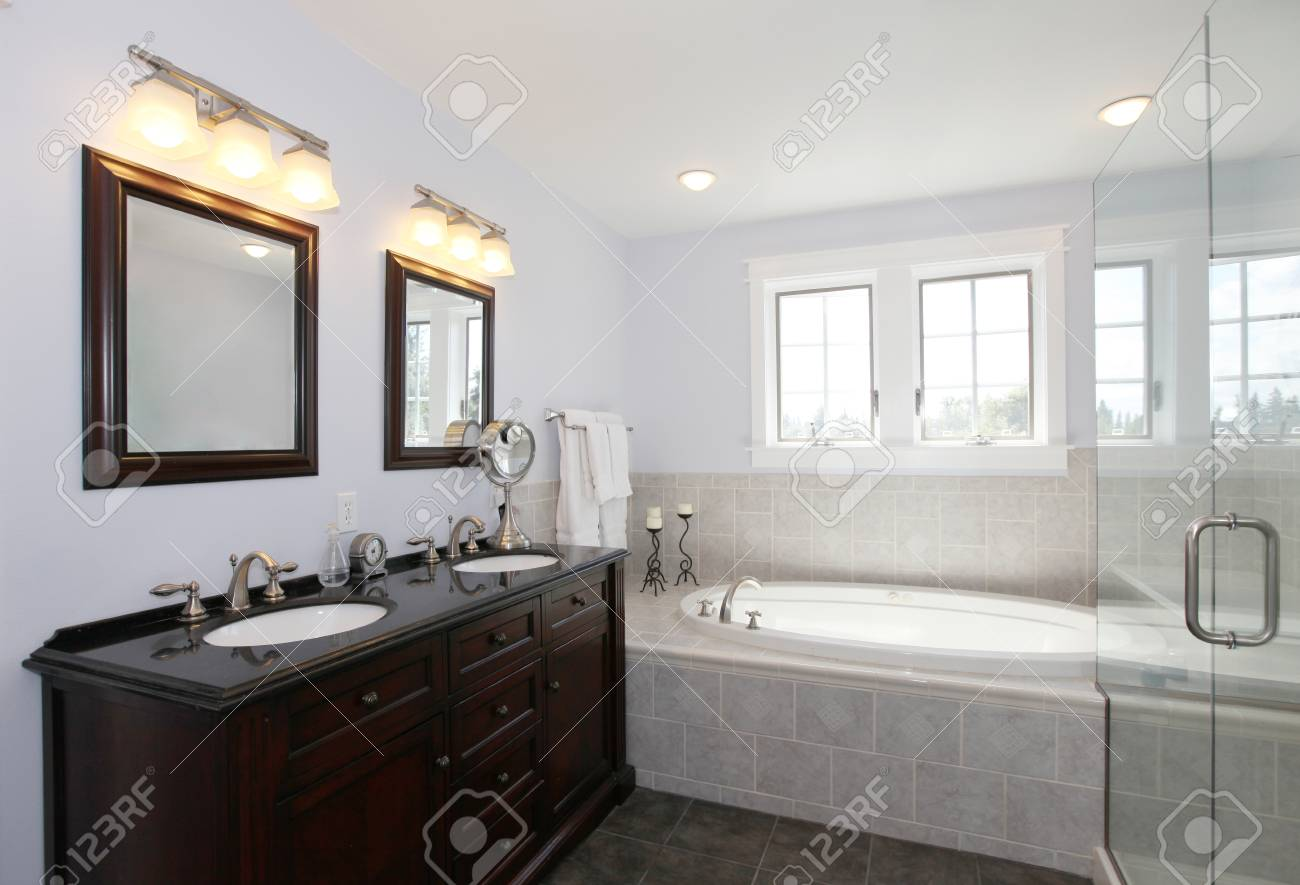 Nice Dark Brown Bathroom With Tub And Wood Cabinet With Two Sinks ...