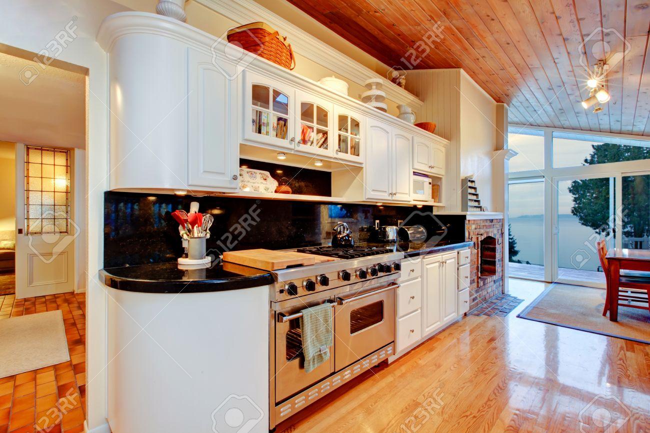 muebles de cocina blancas con encimeras negras piso de madera brillante y techo de madera