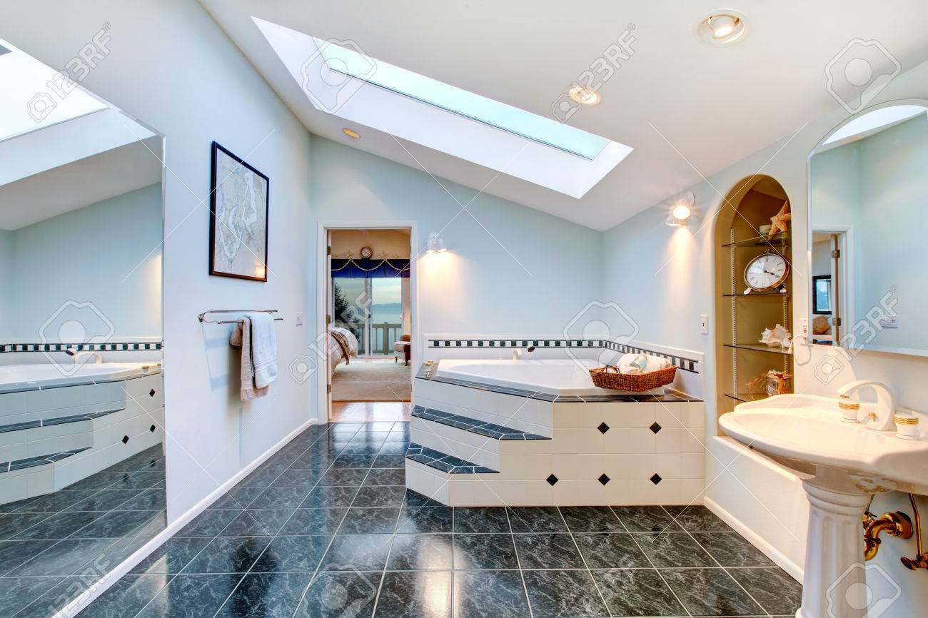 Master Bathroom With Blue Marble Tile Floor, Corner Bath Tub With Stairs  And Tile Trim