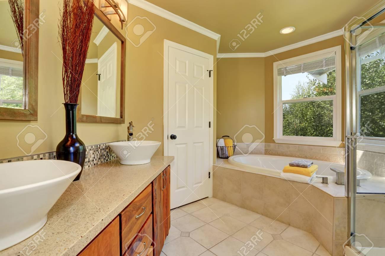 Luxuriöses Badezimmer Interieur In Warmen Beige Farbe, Badewanne Mit  Fliesenverkleidung Und Zwei Weiße Waschbecken Auf