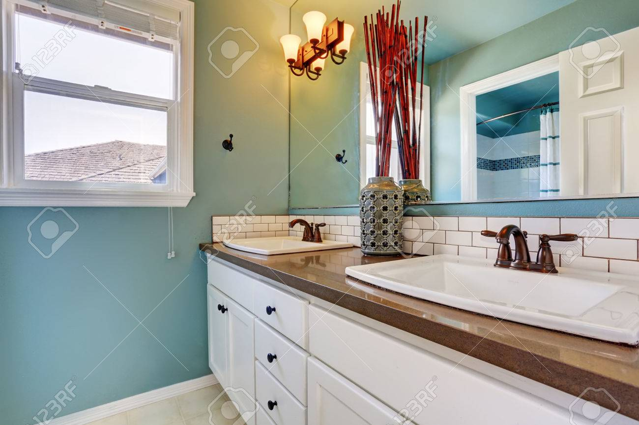 Intérieur de salle de bain blanc et bleu avec une fenêtre et deux lavabos.  Northwest, États-Unis