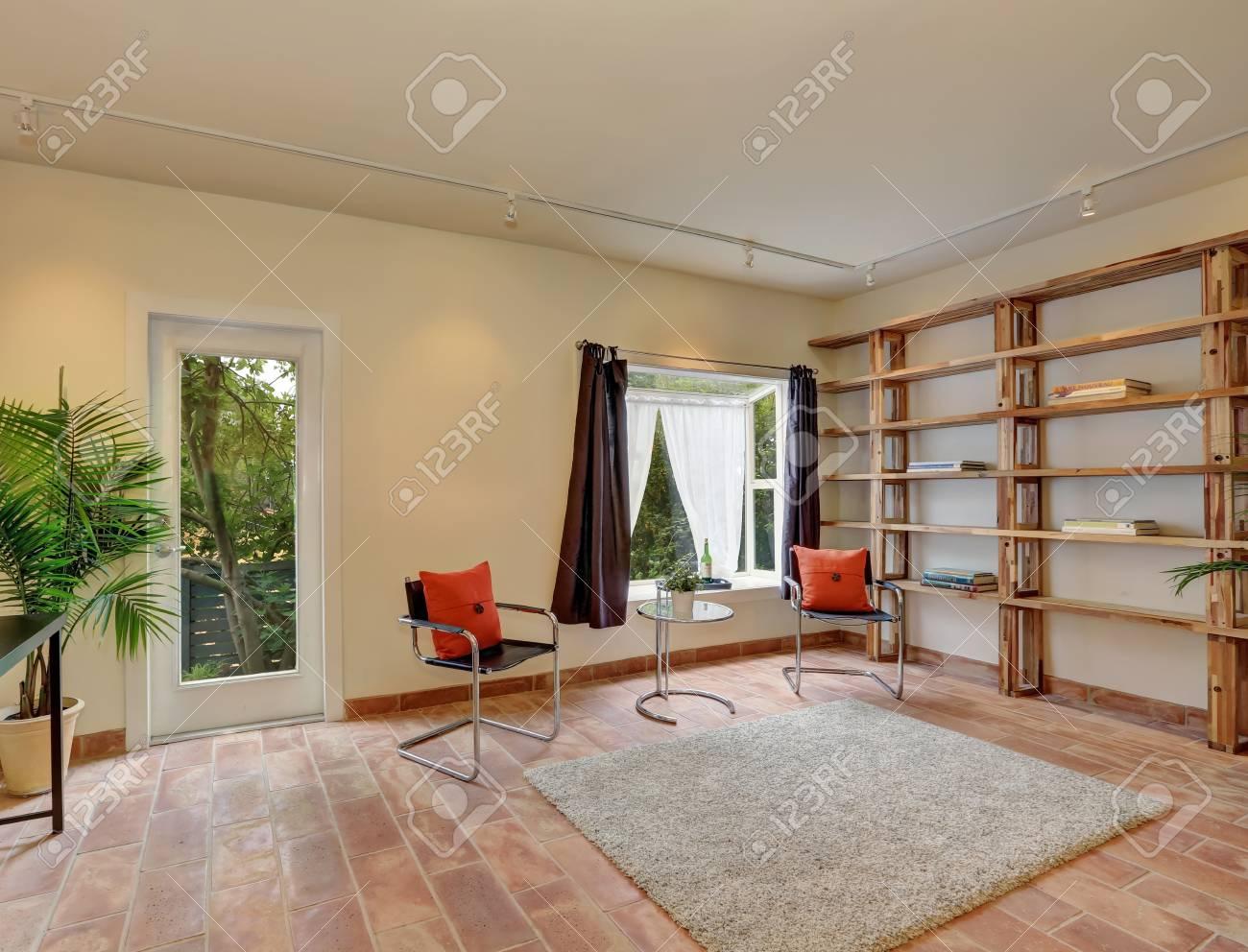 Salon confortable avec des chaises modernes, carrelage, tapis et étagères  de livres dans la maison. Northwest, États-Unis