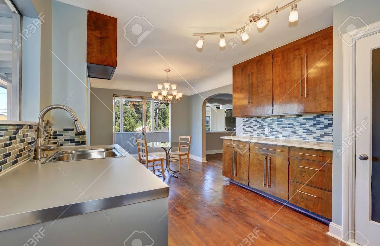 Cucina con sala da pranzo interna. Tavolo da pranzo con piano in vetro e  due sedie di acero. Cucina è dotata di piano cottura in acciaio e mosaico  di ...