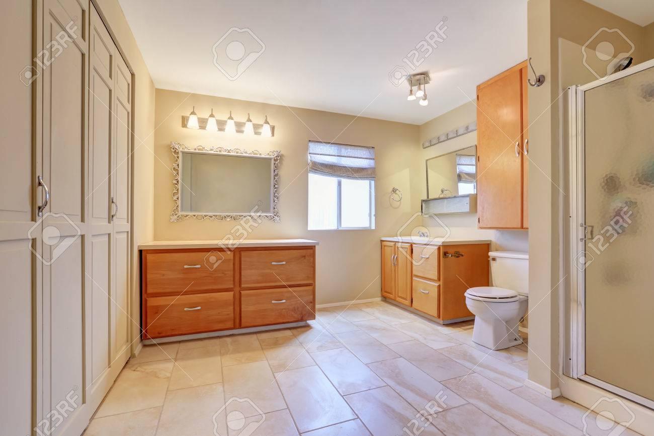 Grande salle de bain lumineuse de couleur beige avec carrelage. Combinaison  de rangement intégrée, deux armoires de toilette et douche en verre. ...