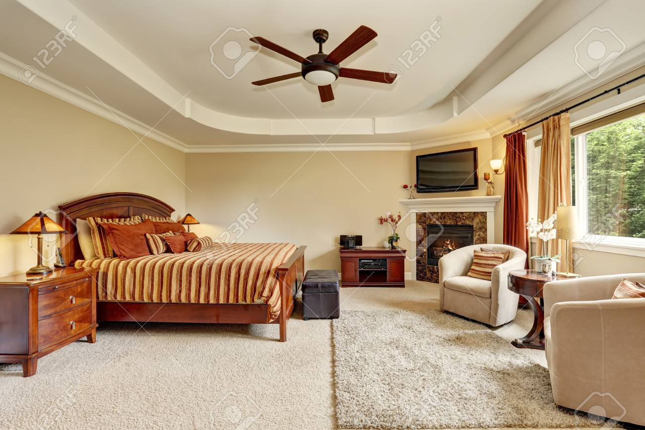 Master bedroom interior with corner fireplace and king size wooden..