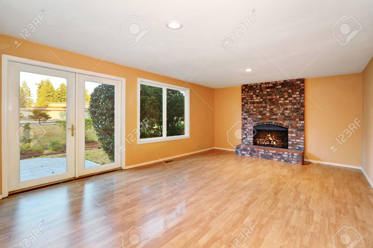 empty living room interior with brick fireplace and shiny hardwood
