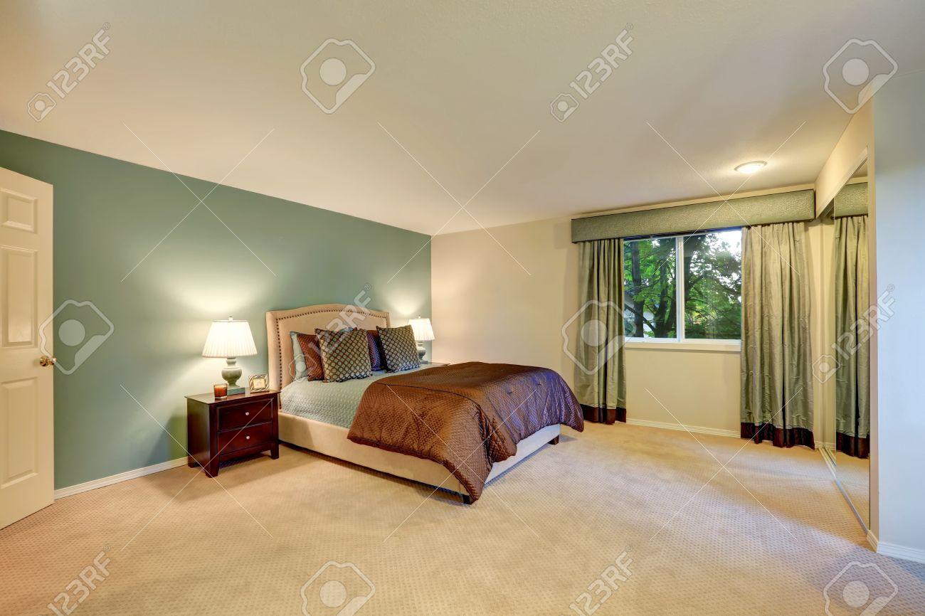 Mint Und Braun Schlafzimmer Mit Beige Teppichboden. Ausgestattet Mit  Nachtschränkchen Und Bett Mit Kopfteil.