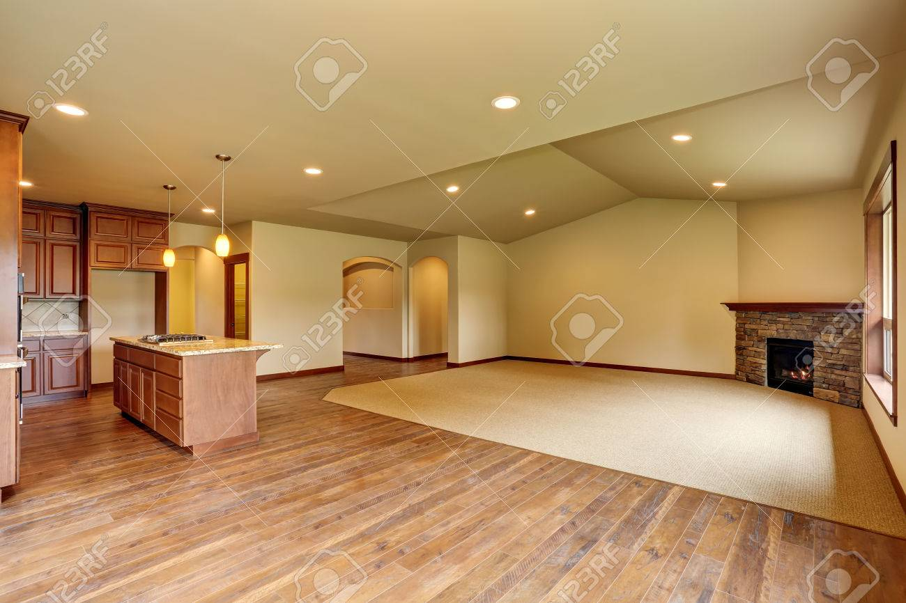 Empty living room with carpet - Empty Living Room With Carpet Floor Connected To Kitchen Area