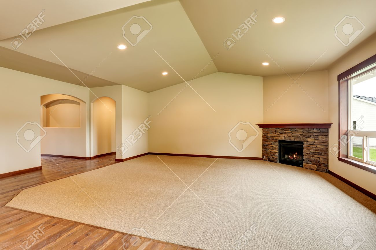 Open floor plan. Empty living room with fireplace, and carpet..