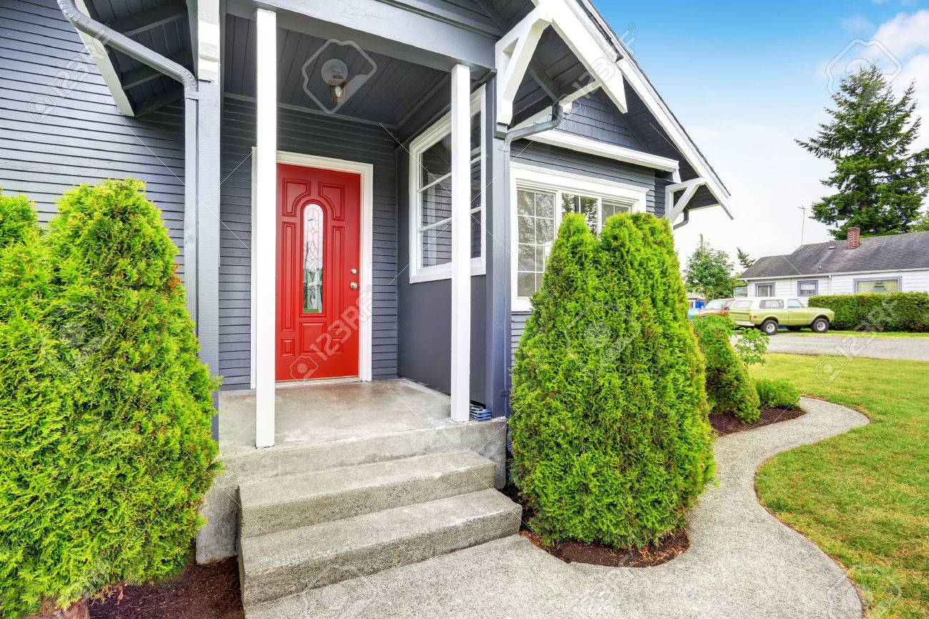 Classic American House Exterior With Siding Trim, Red Entry Door And  Concrete Floor Porch.