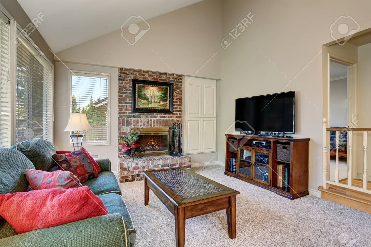 Traditional living room interior with green sofa and brick fireplace...