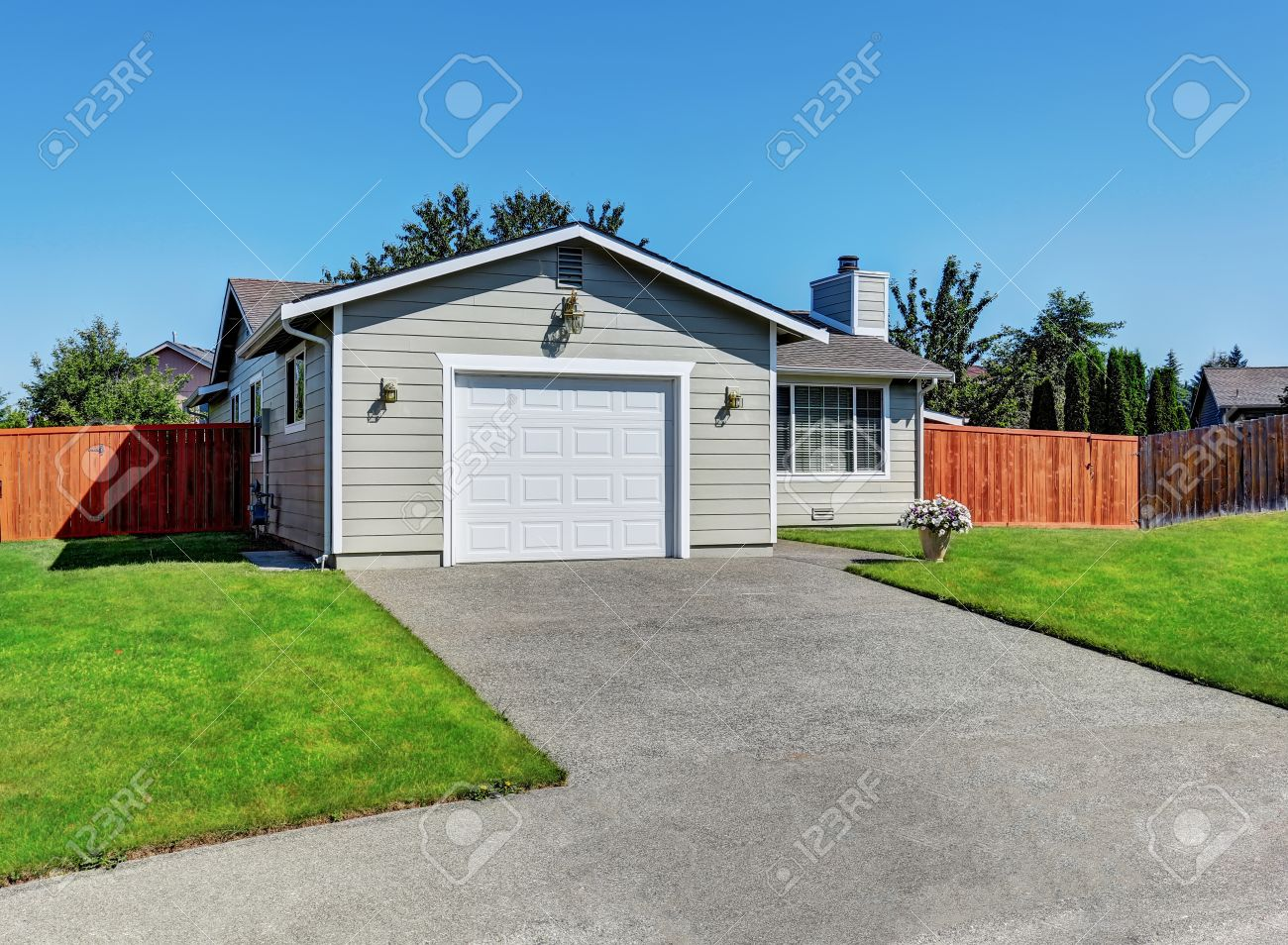 Exterior Of American One Level Rambler House With White Garage Door And Red  Fence. Northwest