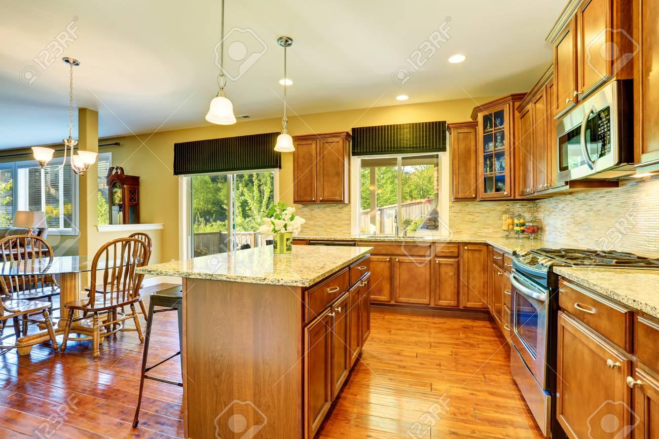 Wooden kitchen interior with kitchen island, steel appliances,..
