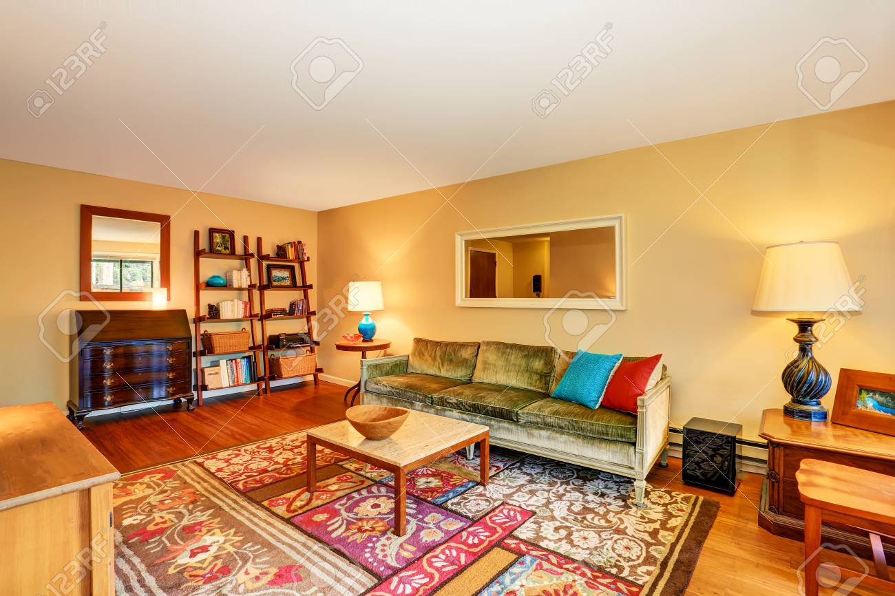 Traditional living room interior with green sofa, hardwood floor..