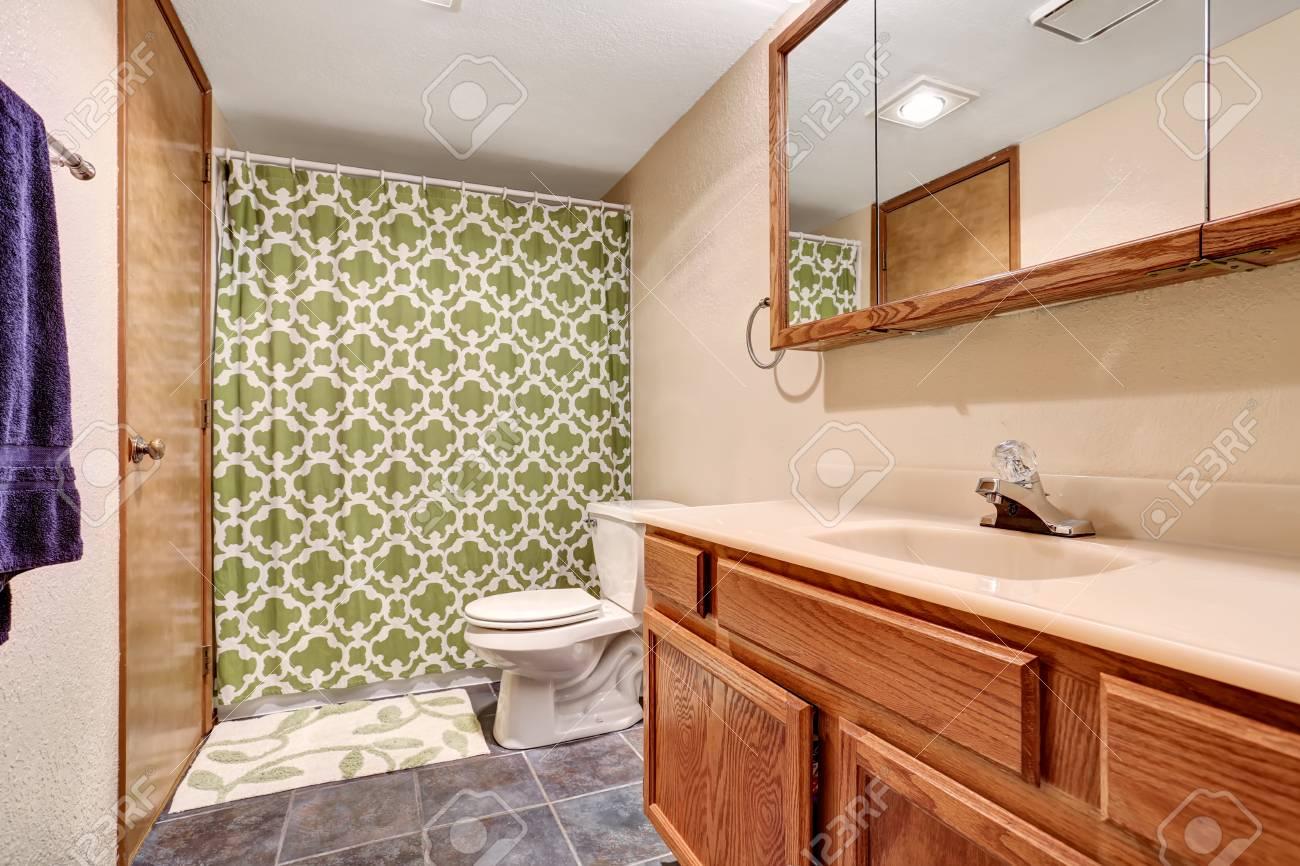 Interno bagno con vanità pavimento di piastrelle e tenda verde