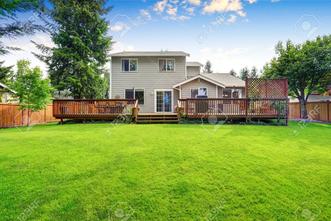 Back Yard House Exterior With Spacious Wooden Deck With Patio Area And  Attached Pergola. Northwest