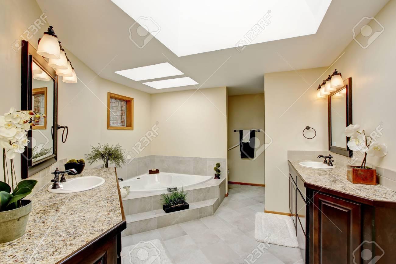 Salle de bain moderne avec deux armoires de vanité avec comptoir en granit  et baignoire blanche. Northwest, États-Unis