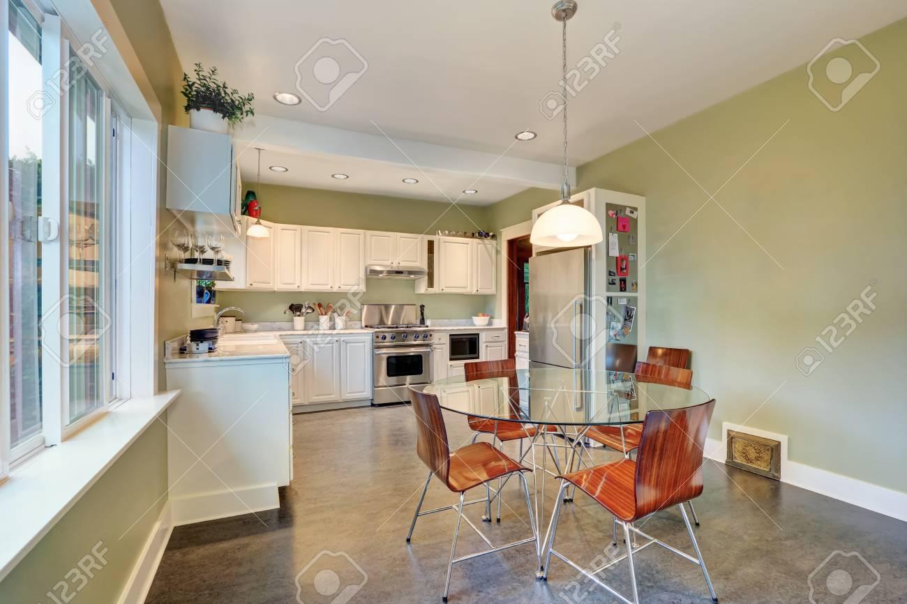 Vista del tavolo con piano in vetro e sedie moderne. Inoltre combinazione  di mobili da cucina bianco nella parte posteriore. Northwest, Stati Uniti  ...