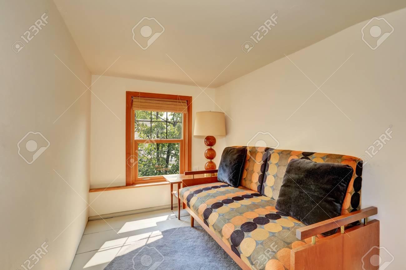 Petite chambre à l\'étage avec orange vif et un canapé noir. Northwest,  États-Unis