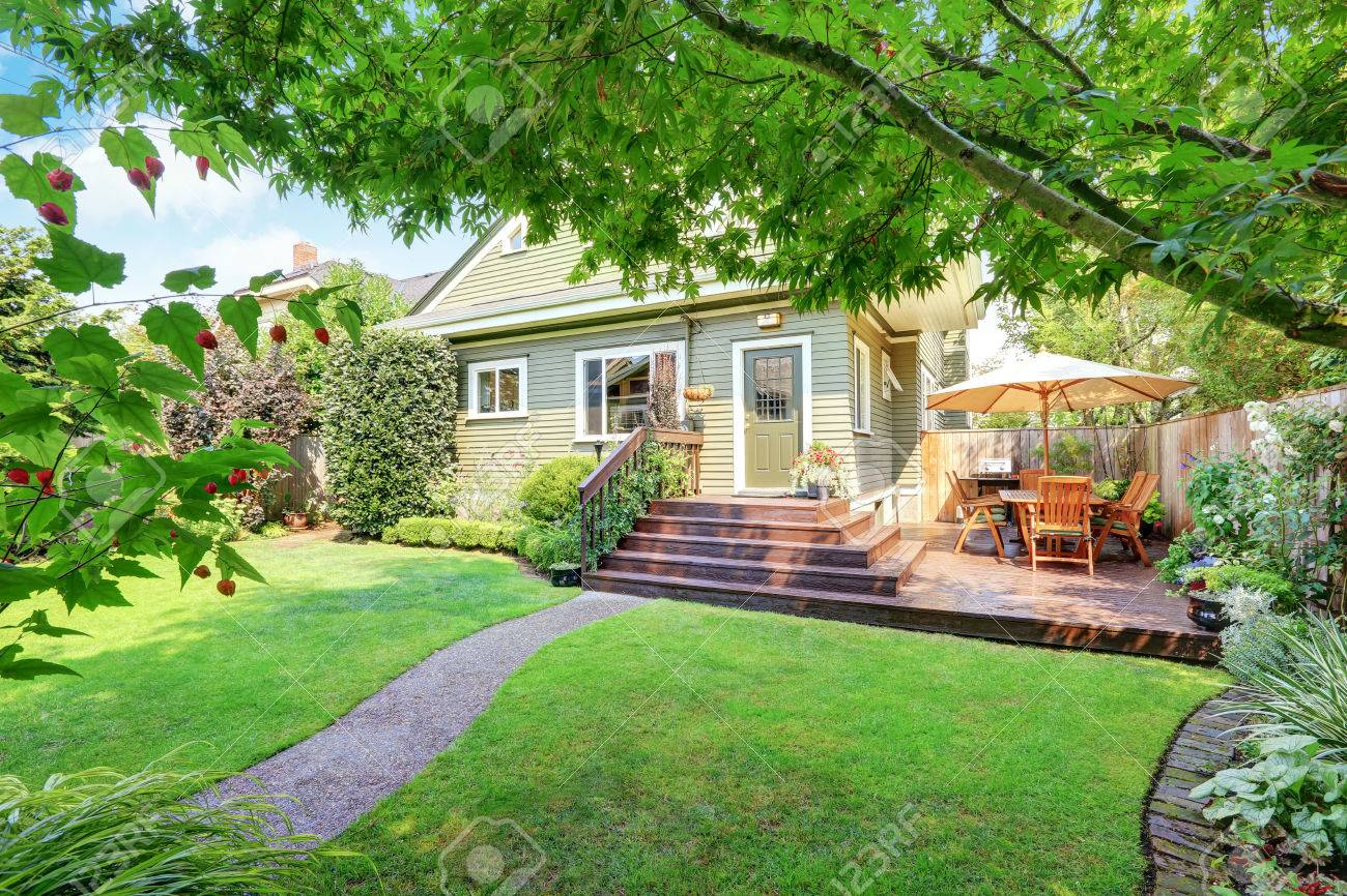 Backyard area with walkout deck, patio table set and well kept lawn. Northwest, USA - 61647611