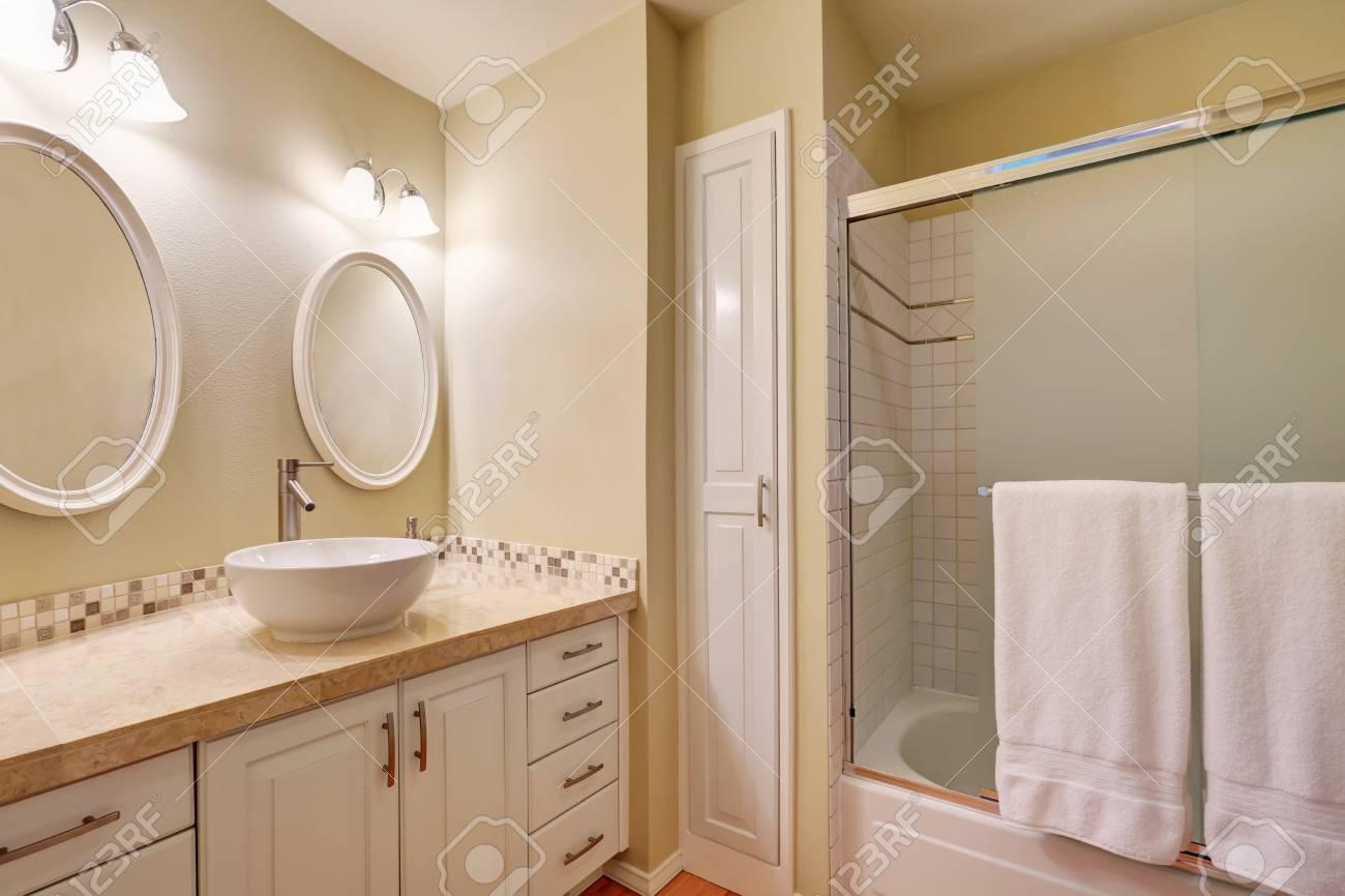 Intérieur salle de bain classique avec des murs crème, évier blanc avec un  design moderne et blanc meuble-lavabo. Northwest, États-Unis