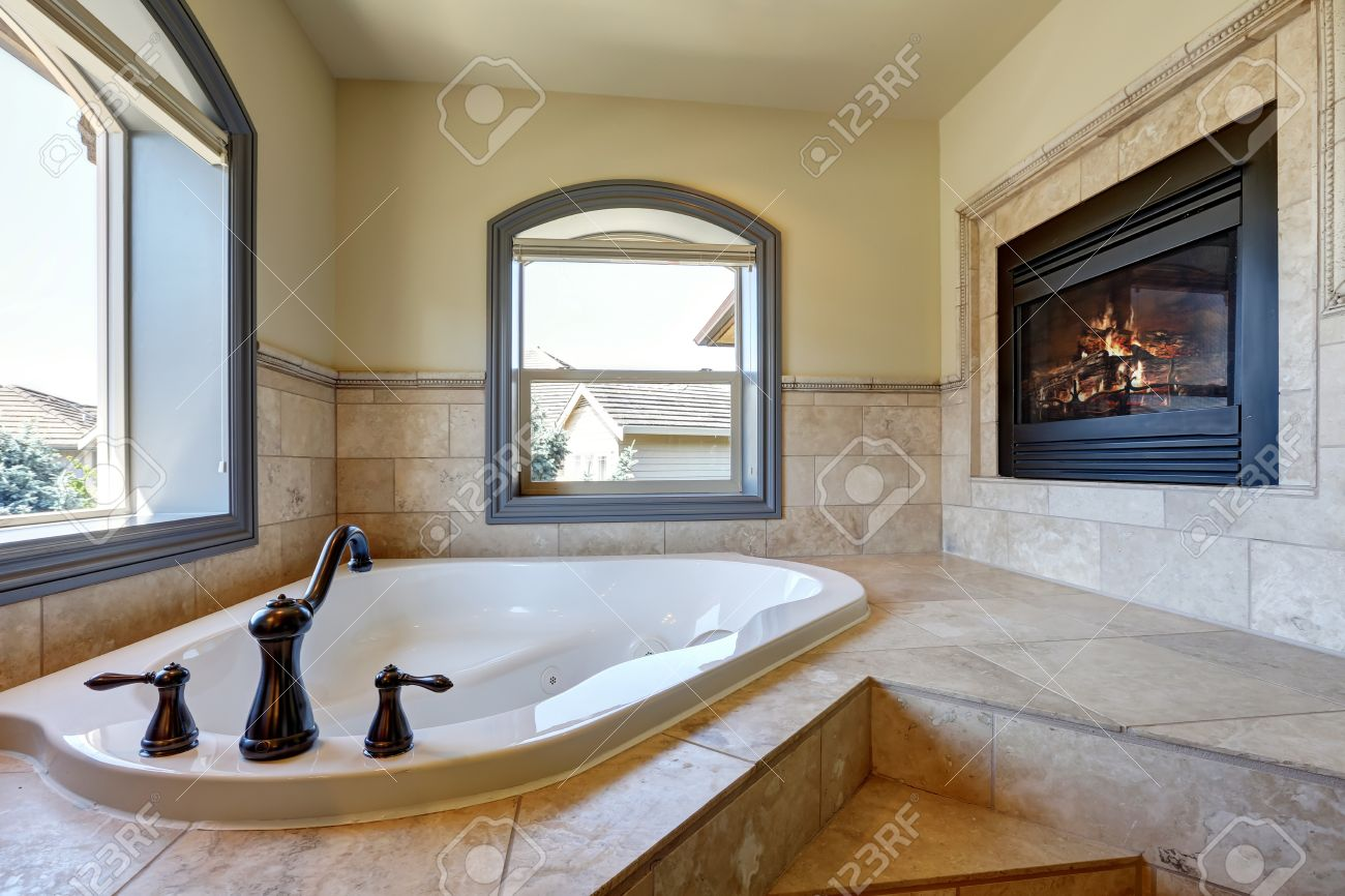 Great Bathroom Interior In Luxury House With Fireplace, Corner Bathtub With  Stairs And Tile Trim
