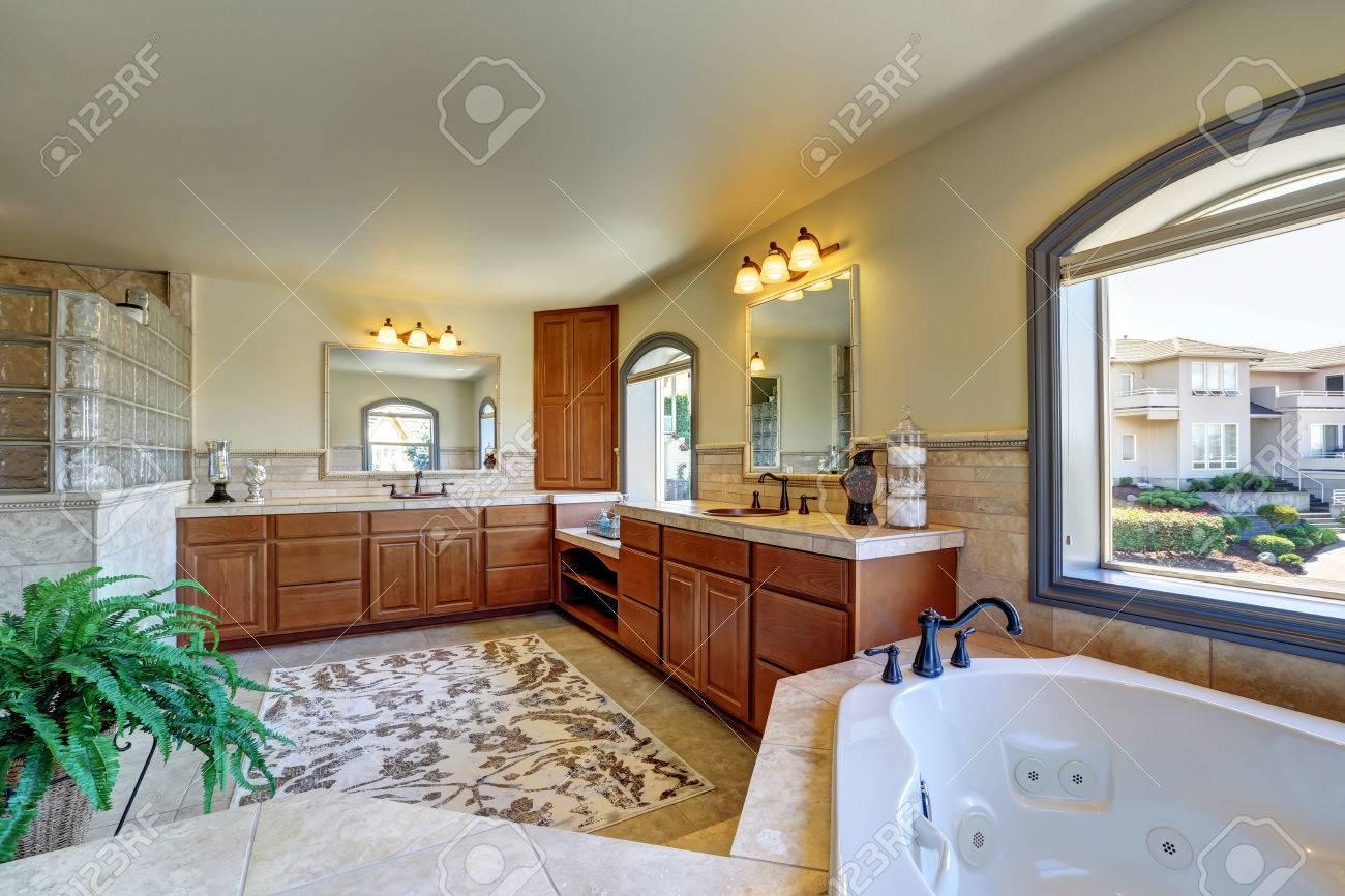Intérieur salle de bains Grande maison de luxe avec coin baignoire et  maître des armoires en bois avec deux lavabos. Northwest, États-Unis