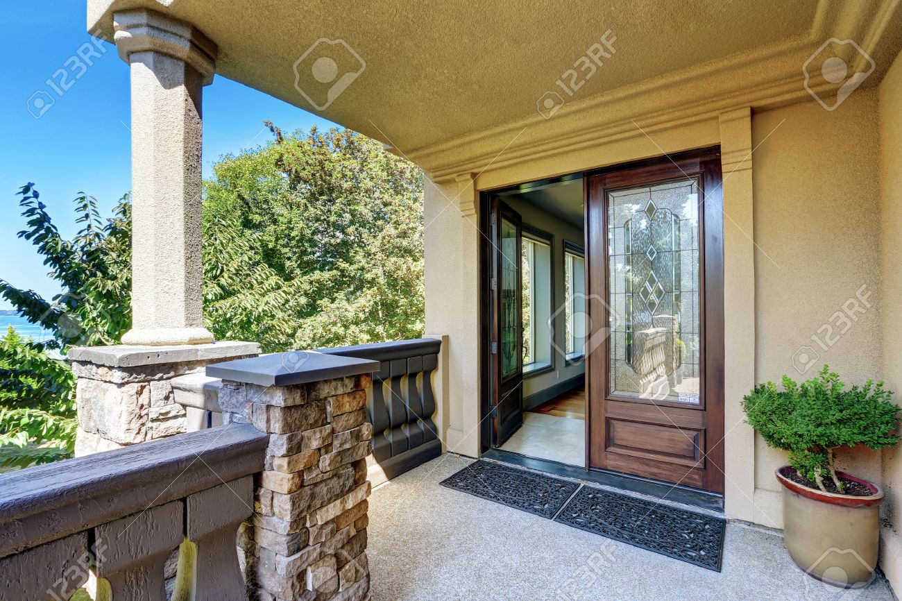 Luxury House Exterior. Entrance Column Porch With Railings And Rug Open Front  Door. Northwest