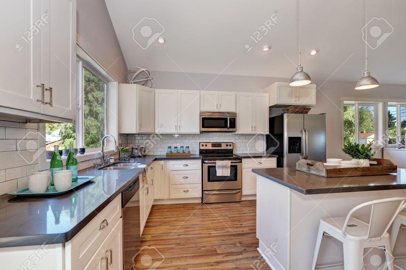 Intérieur de la cuisine avec plafond voûté élevé, feux pendants, armoires  de cuisine blanches et appareils en acier. Nord-Ouest, États-Unis