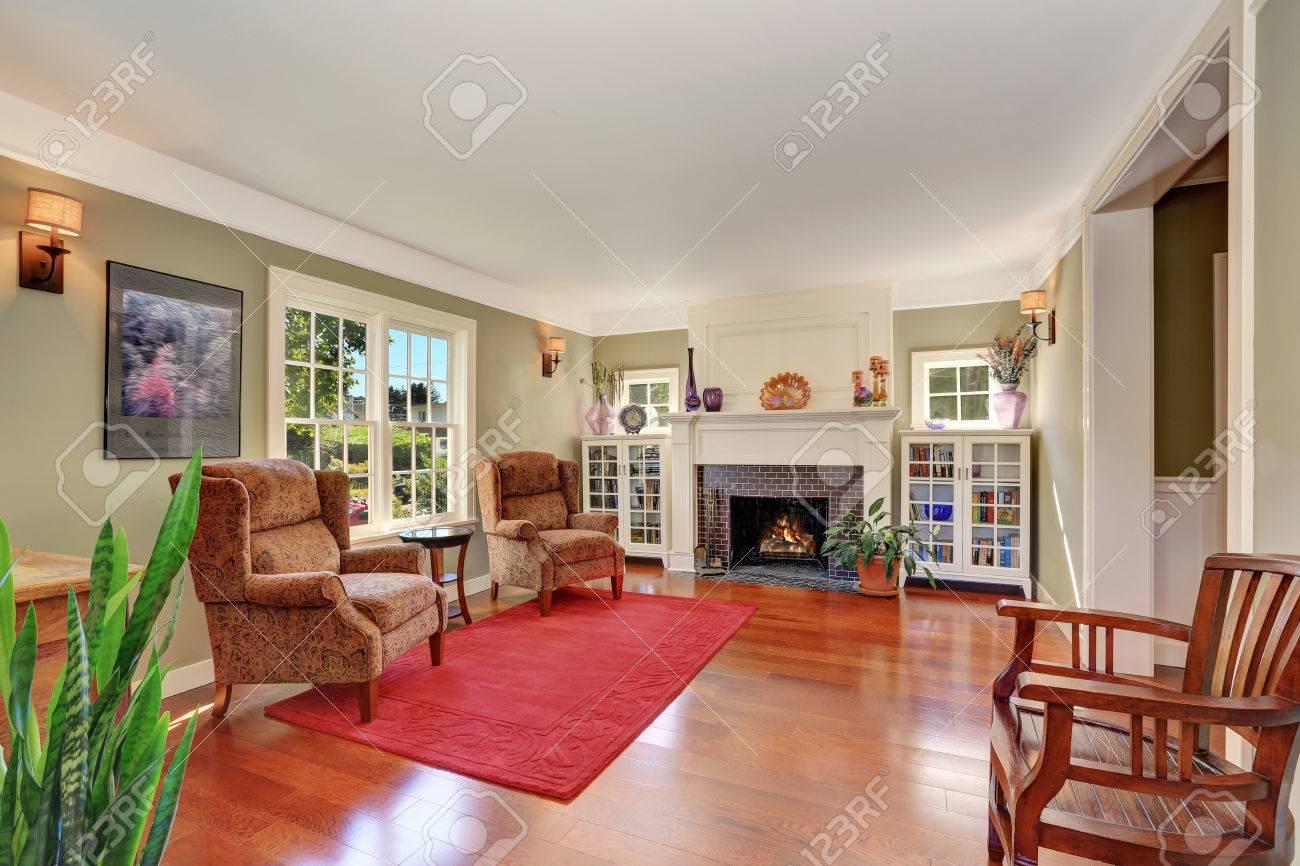 Bel salon avec mobilier ancien et tapis rouge. Aussi cheminée en brique,  deux librairies et grande fenêtre française. Nord-Ouest, États-Unis