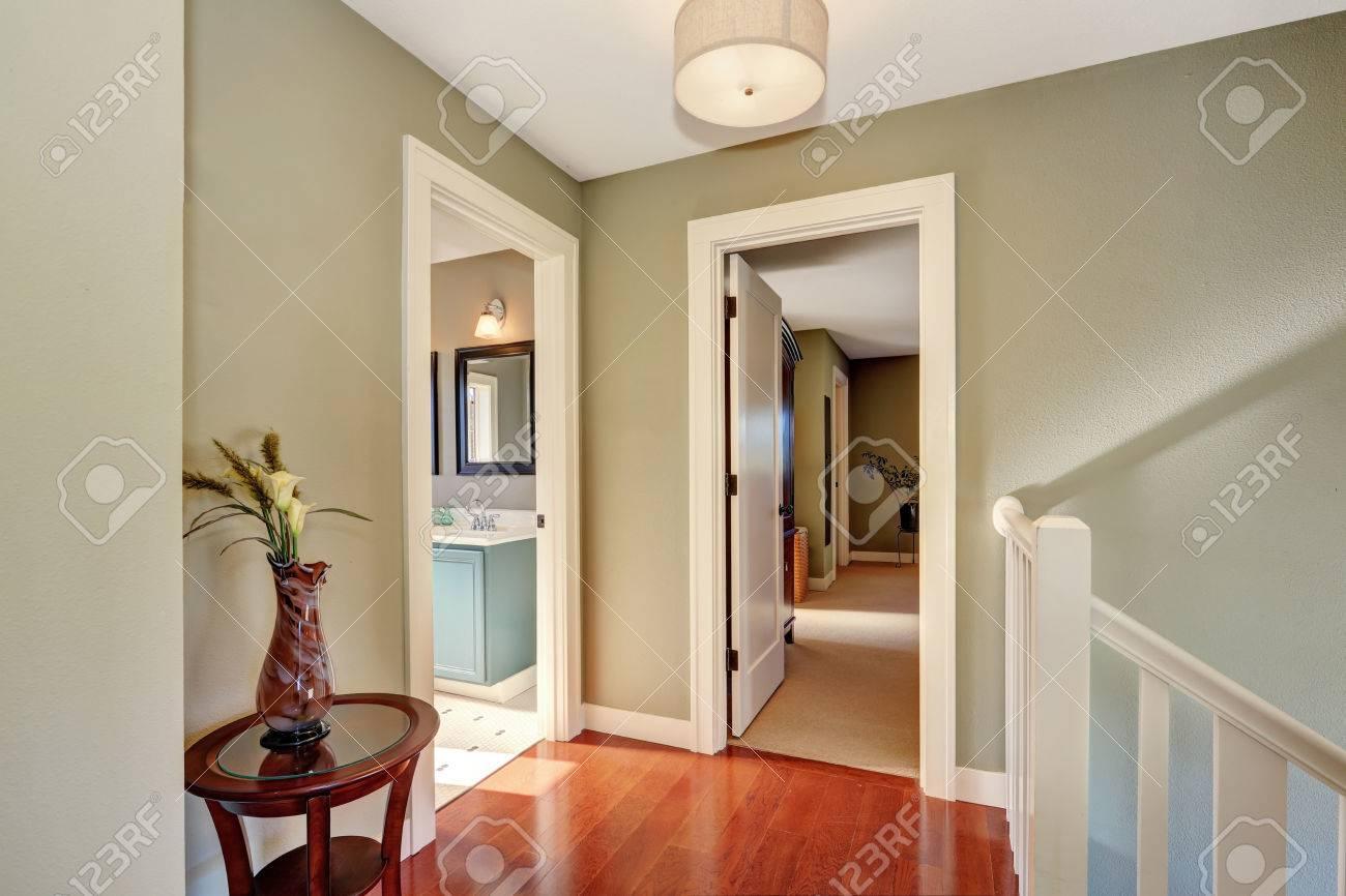 Hallway With Olive Walls And Hardwood Floor. Open Doors To Bathroom ...