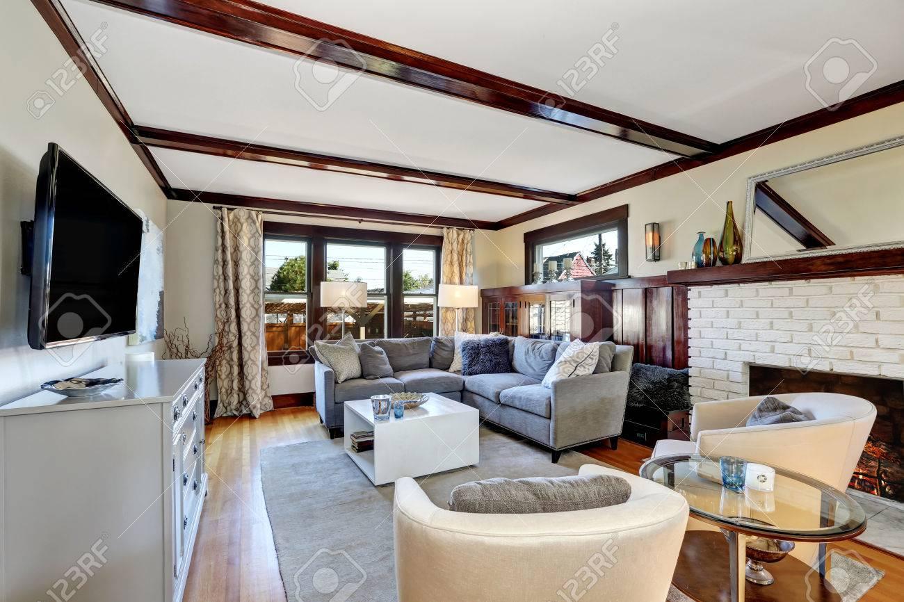 Table Basse Grand Salon intérieur de salon américain luxueux dans les tons gris et marron. meublé  avec un grand canapé d'angle, des armoires vintage et une table basse.