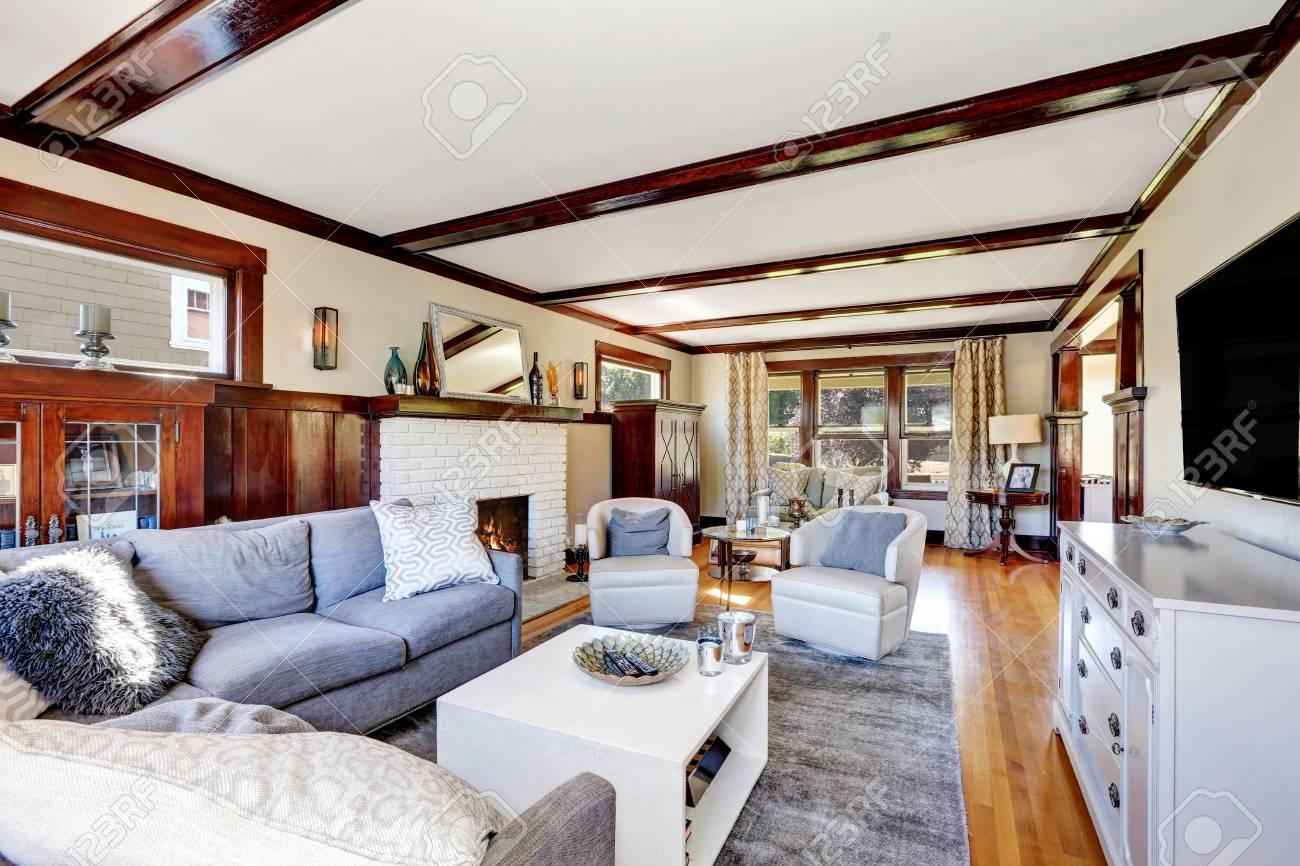 Intérieur de salon américain luxueux dans les tons gris et marron. Meublé  avec un grand canapé d\'angle, des armoires vintage et une table basse. ...
