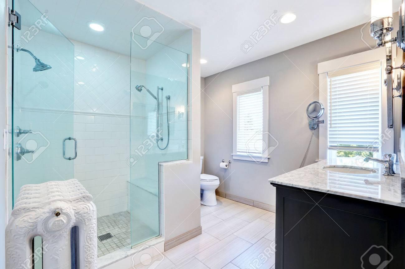 Salle de bain rafraîchissant avec grande promenade en verre dans la douche  avec deux têtes et le radiateur en fonte dans le style rétro. Northwest, ...
