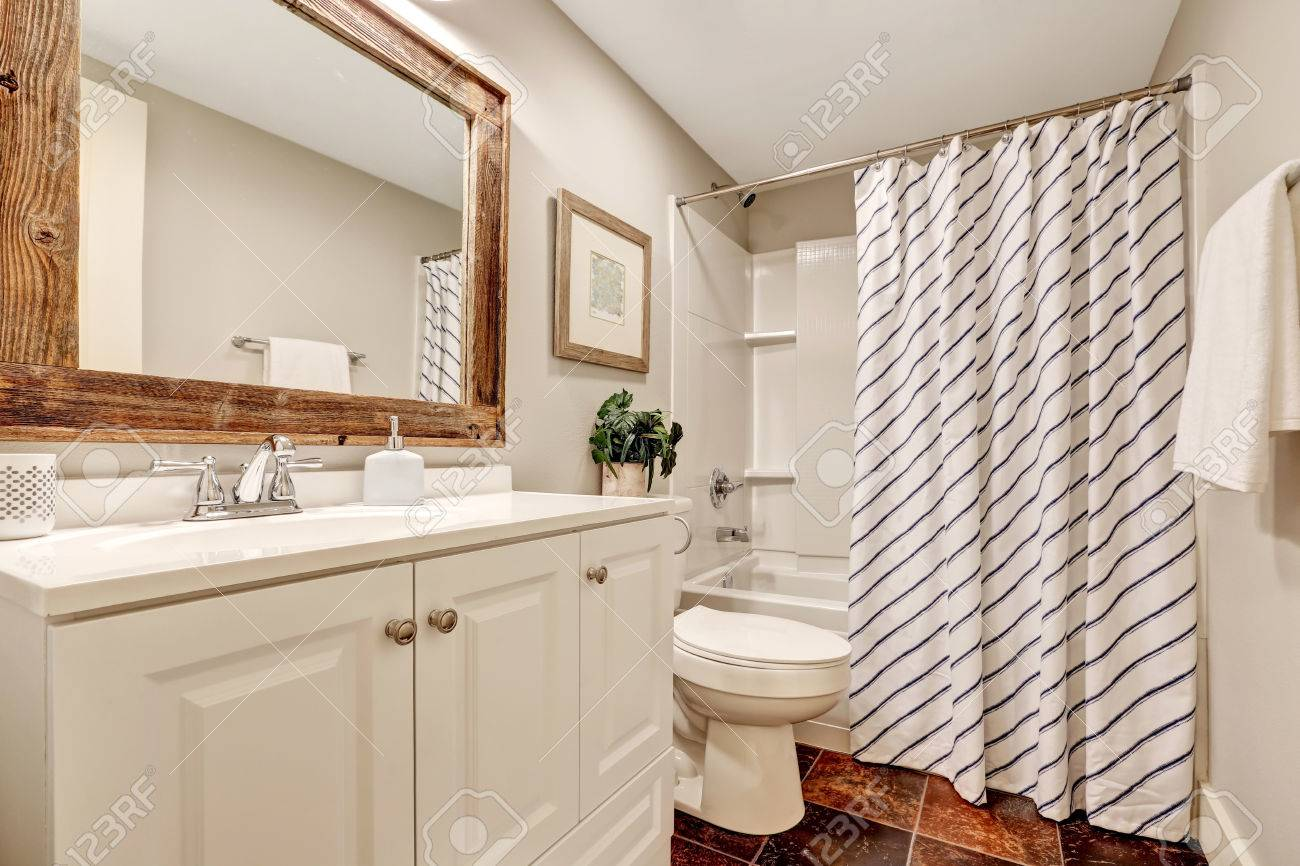 White Tones Bathroom With Vanity Cabinet And Wooden Framed Mirror ...