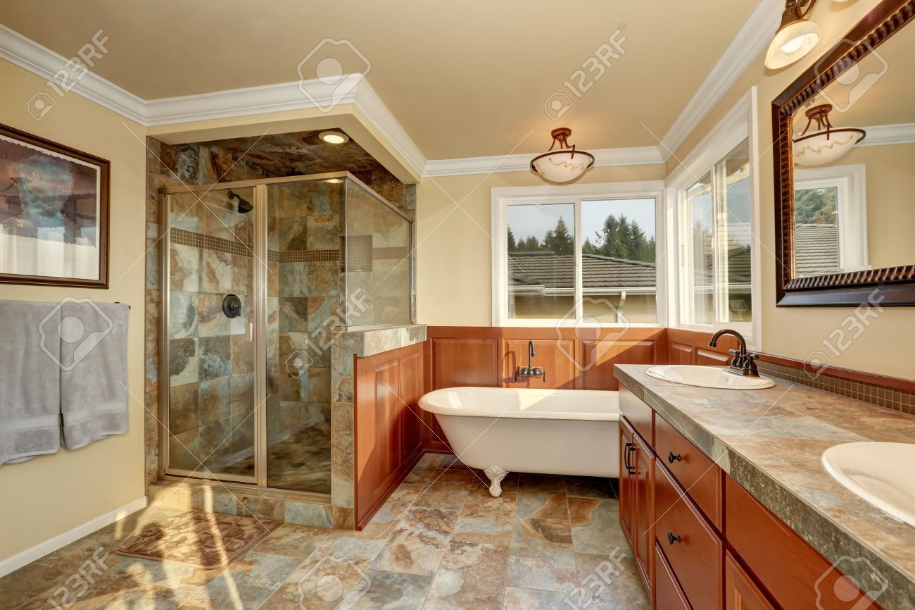 Bathroom With Natural Stone Tile And Beige Walls. Glass Corner ...